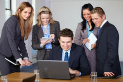 Team of 5 business people during meeting. One men sitting and work on the laptop while other make some remarks Royalty Free Stock Images