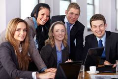Team of 5 business people during meeting. Blonde female work on her laptop while other make some remarks Royalty Free Stock Photos