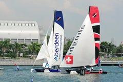 Team Aberdeen Singapore som springer Alinghi på den extrema segla serien Singapore 2013 Royaltyfri Foto