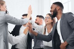 Team achievement, diverse business people giving high five. At meeting royalty free stock image
