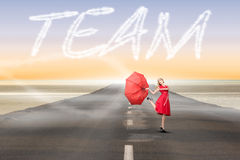 Team against road leading out to the horizon Stock Image