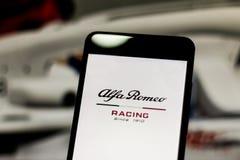 Team Alfa Romeo Racing Formula 1 logo på mobil enhetskärmen Alfabetisken Romeo Racing bekämpar världsmotorsportmästerskapet royaltyfri foto