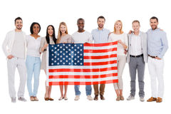 Team of America. Full length of happy diverse group of people bonding to each other and holding flag of America while standing against white background together Stock Photography