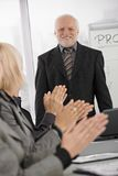 Team applauding senior businessman in office stock photo