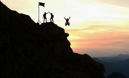 Team arbete, livmål och självförbättringsbegreppet Man som hjälper hans kvinnliga klättringpartner upp en brant kant av ett berg arkivfoton