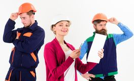 Team of architects, builders with woman manager,. Boss looks at document, isolated white background. Woman in hard hat with smiling face manages mens team of royalty free stock image