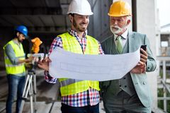 Team of architects and engineer in group on construciton site check documents and business workflow stock photography