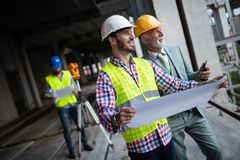 Team of architects and engineer in group on construciton site check documents and business workflow royalty free stock photo