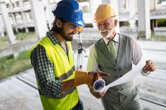 Team of architects and engineer in group on construciton site check documents and business workflow royalty free stock image