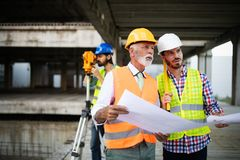 Team of architects and engineer in group on construciton site check documents and business workflow stock photo