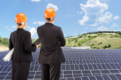 Team of architects examining solar panels under sunny sky Royalty Free Stock Images