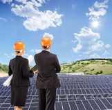 Team of architects examining solar panels under sunny sky Stock Image