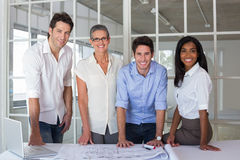 Team of architects going over blueprints smiling at camera Stock Photo