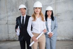 Team of architects in helmets holding blueprints and looking at camera Royalty Free Stock Image