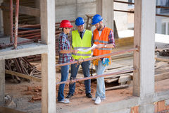 Team of architects looking plan at site Royalty Free Stock Image