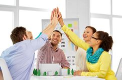 Team of architects making high five at office. Architecture , construction and people concept - creative team of architects or designers with project blueprint stock photography