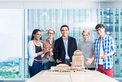 Team of architects presenting model building. In presentation to customer Stock Image