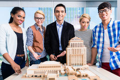 Team of architects presenting model building Stock Image