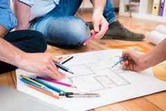 Team of architects sitting on floor with construction plans Stock Photos