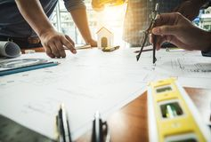 Team of architecture engineer construction with paper plan project housing. royalty free stock image