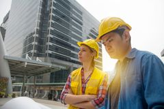 Team of architectures standing at construction site looking at p stock photography