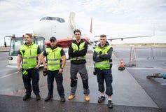 Team With Arms Crossed Standing moulu contre l'avion photo libre de droits