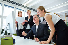 Team around monitor with touchscreen in office Royalty Free Stock Photography