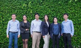 Team of Asian business man and woman looking at camera with smiling face outside office at green leaf wall. stock images
