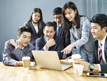 Asian corporate people reviewing business results. Team of asian corporate people reviewing business result using laptop computer in office royalty free stock photography