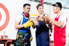 Team of Asian workers discussing product Stock Image