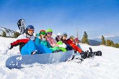 Team avec des surfs des neiges et des lunettes se reposant dans une rangée Images stock