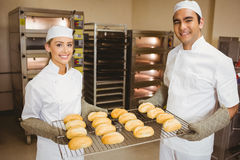 Team of bakers holding rack of rolls Royalty Free Stock Photos