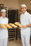 Team of bakers holding rack of rolls Stock Image