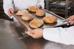 Team of bakers holding trays of bread Stock Photography