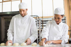 Team of bakers preparing dough Stock Images