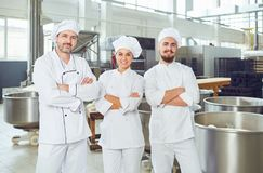 A team of bakers smiles at the bakery. A team of bakers smiles, looks into the camera at the bakery stock image
