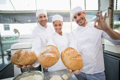 Team of bakers smiling at camera holding bread Stock Photos