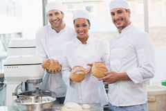 Team of bakers smiling at camera holding bread Stock Photo
