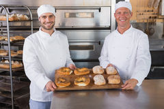 Team of bakers smiling at camera with trays of bread Stock Image