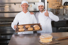 Team of bakers smiling at camera with trays of croissants Stock Photo