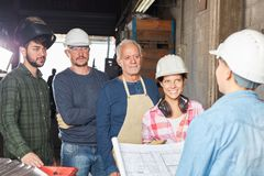 Team of blue collar workers in meeting. Planning operation stock image