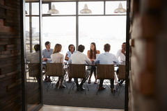 Team in a boardroom meeting seen through open doors, full length Royalty Free Stock Photos