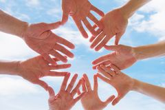 Team or brotherhood concept, group of people putting hands together. Against blue sky royalty free stock photos