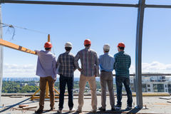 Team Of Builders On Costruction Site Back Rear View, Foreman Group In Hardhat Outdoors Partnership And Teamwork Concept Royalty Free Stock Photos