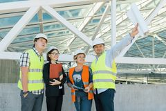 Team of builders engineer architect on the roof of construction site. Building, development, teamwork and people concept.  royalty free stock photo