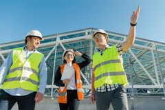 Team of builders engineer architect on the roof of construction site. Building, development, teamwork and people concept.  royalty free stock photography