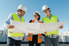Team of builders engineer architect on the roof of construction site. Building, development, teamwork and people concept.  royalty free stock images