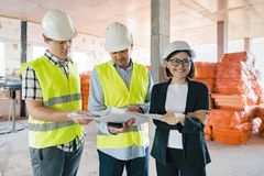 Team of builders engineers at construction site, reading blueprint. Construction, development, teamwork and people concept stock images