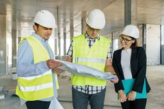 Team of builders engineers at construction site, reading blueprint. Construction, development, teamwork and people concept stock photo