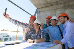 Team Of Builders Happy Smiling Take Selfie Photo During Meeting With Architect And Engineer On Construction Site. Discussing Buiding Plan royalty free stock photo